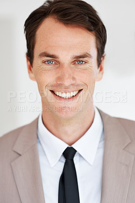 Buy stock photo Portrait of a successful young businessman in suit smiling at work