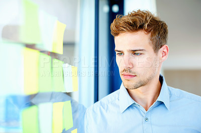 Thoughtful guy looking at adhesive notes