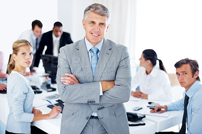 Buy stock photo Portrait of a senior manager with his business team sitting behind working at office