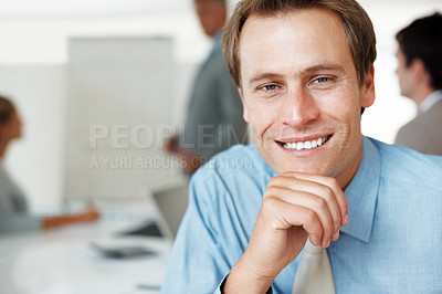 Buy stock photo Closeup portrait of a smart young businessman smiling and his colleagues working at the back