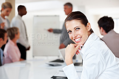 Buy stock photo Portrait of a smiling young businesswoman smiling and her colleagues working on presentation at office