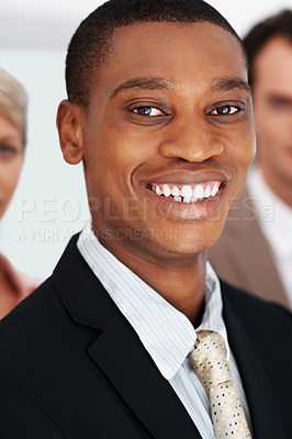 Buy stock photo Portrait of a happy young black businessman with his colleagues at the back