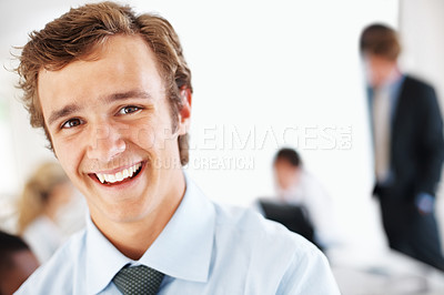 Buy stock photo Portrait of a smart young businessman smiling and his colleagues working behind at office