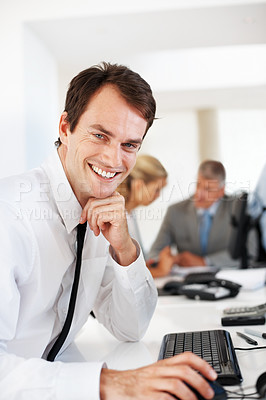 Buy stock photo Smiling young businessman working on computer with his colleagues discussing in background