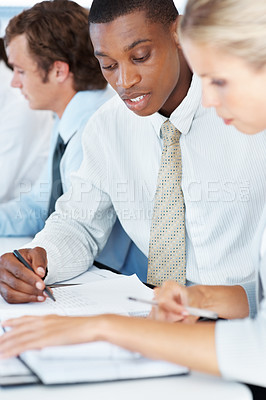 Buy stock photo Portrait of a american african businessman sitting at a business meeting with colleagues in office