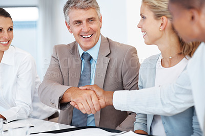 Buy stock photo Mature businessman shaking hands to seal a deal with his partner and colleagues