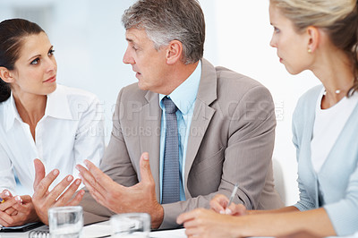 Buy stock photo Portrait of a mature businessman guiding his colleagues in a meeting at office