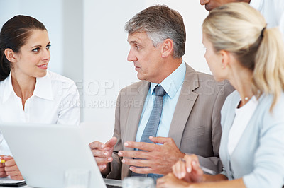 Buy stock photo Confident mature businessman explaining a business project on laptop to his colleagues