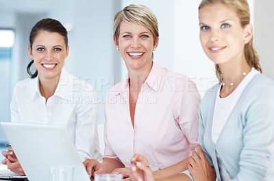 Buy stock photo Portrait of happy team of businesswomen sitting at office desk with laptop