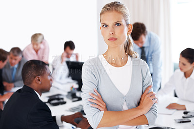 Buy stock photo Smart young businesswoman standing with hands folded and her colleagues working behind
