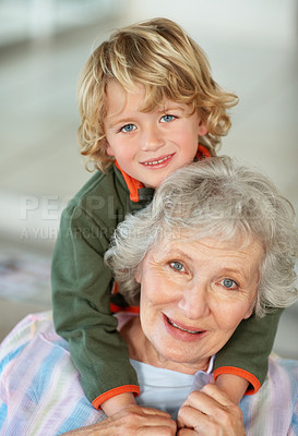Buy stock photo Portrait of a senior woman giving her grandson a piggyback ride