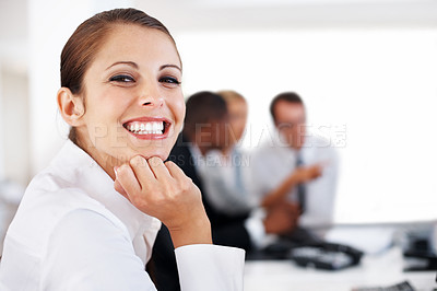 Buy stock photo Portrait of a smiling young businesswoman with her colleagues working at the back