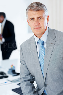 Buy stock photo Portrait of a successful middle aged businessman sitting on his desk at office