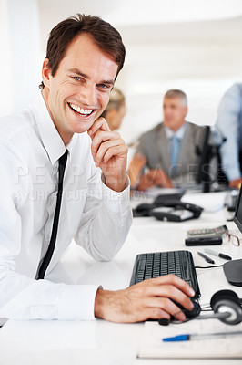 Buy stock photo Successful young businessman working on computer with colleagues behind at office