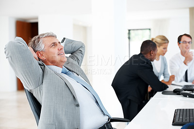 Buy stock photo Mature businessman taking break form work with colleagues working in background