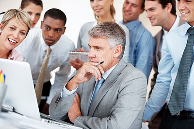Buy stock photo Smart mature business executive in front of laptop with colleagues surrounding him