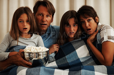 Buy stock photo Shocked family of four sitting on a sofa watching a horror movie with bed sheet and popcorn
