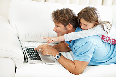 Buy stock photo Father and daughter lying on top of each other using laptop and pointing at the screen