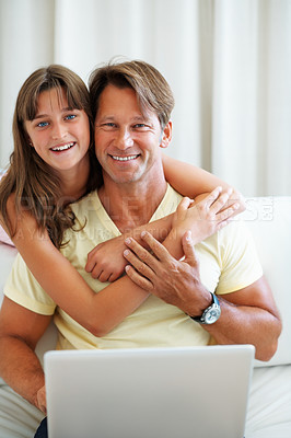 Buy stock photo Portrait of father sitting on a sofa using laptop with daughter hugging him from behind