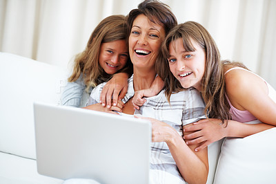 Buy stock photo Mother and children smiling and using laptop while sitting on sofa