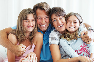Buy stock photo Family of four sitting together on sofa and smiling with man hugging them