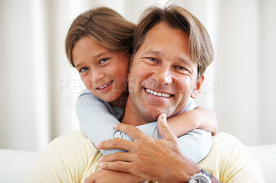 Buy stock photo Closeup portrait of father sitting on a sofa with daughter hugging him from behind