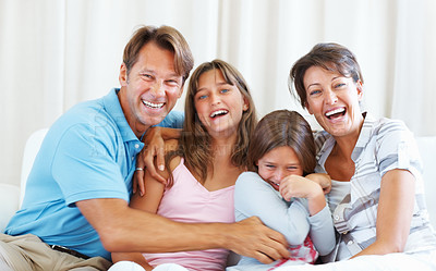 Buy stock photo Portrait of family sitting on a sofa and having fun together