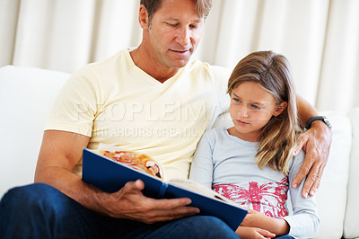 Buy stock photo Father and daughter sitting on a sofa and reading a story book