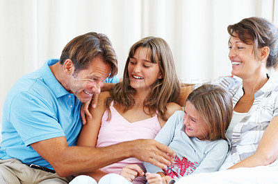 Buy stock photo Family of four sitting on a sofa with father tickling his younger daughter