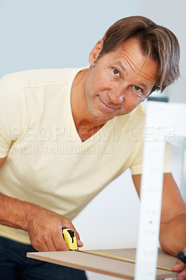 Buy stock photo Portrait of man building shelf and measuring wooden board with a measuring tape