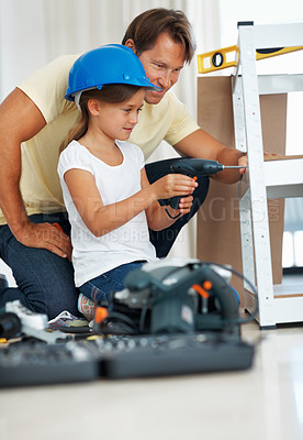 Buy stock photo Man assisting his daughter in using a power drill while building a shelf