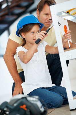 Buy stock photo Young girl using hammer with father helping her while building shelf