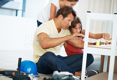 Buy stock photo Man building a shelf and showing the reading displayed on the digital angle measurer to his daughters