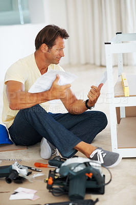 Buy stock photo Full length of a man reading instructions for building a shelf