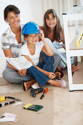Buy stock photo Portrait of a smiling family sitting together while building a shelf