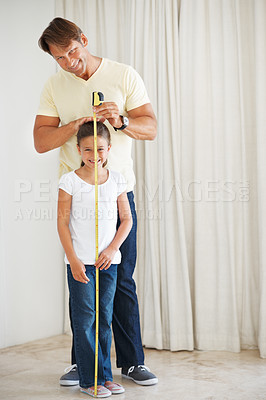 Buy stock photo Full length of father measuring the height of his daughter using a measuring tape