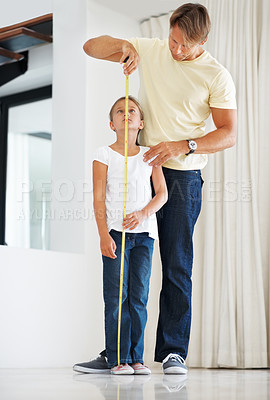 Buy stock photo Full length of father holding an extended measuring tape against his daughter and measuring her height
