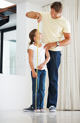 Buy stock photo Full length of young girl getting her height measured with the help of her father