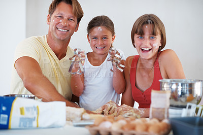 Buy stock photo Portrait of family preparing cookies in the kitchen and smiling with girl showing man shaped cutter