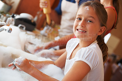 Buy stock photo Portrait of smiling girl doing the washing up with her father and sister