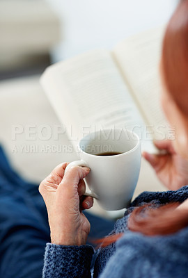 Buy stock photo Top view of a mature woman holding a cup of tea while reading book
