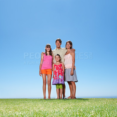 Buy stock photo Full length of family of four standing together on grass and smiling - copyspace