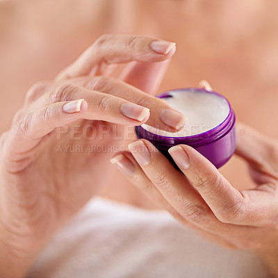 Buy stock photo Cropped studio shot of a woman holding a container of moisturizer