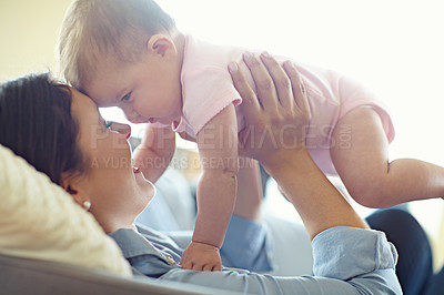 Buy stock photo Shot of a mother lifting her baby girl while lying on the sofe at home