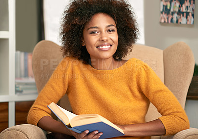 Buy stock photo Cropped portrait of a young woman reading a book on her sofa