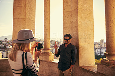 Buy stock photo Shot of a young woman taking a picture of her boyfriend while touring a foreign city