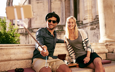 Buy stock photo Shot of a young couple taking a selfie with a selfie stick while taking a break from exploring an old city