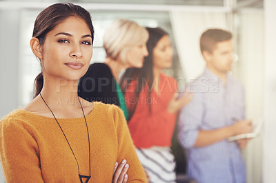 Buy stock photo Cropped portrait of a young businesswoman standing in an office with her team in the background