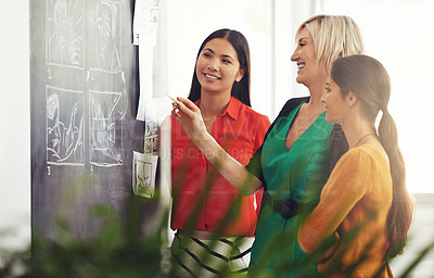 Buy stock photo Cropped shot of three businesswoman strategizing at the blackboard