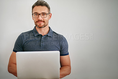 Buy stock photo Shot of a man using a laptop against a gray background